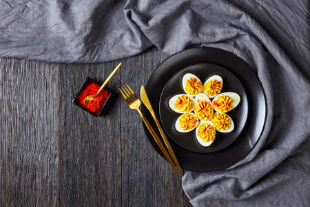 Deviled eggs of hard-boiled eggs halved and filled with smashed egg yolks mustard, mayonnaise, white vinegar sprinkled with smoked paprika on a black plate on a dark wooden background, top view 免版税图像