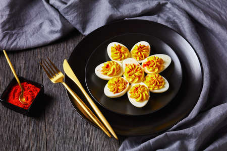 American appetizer deviled egg filled with smashed egg yolks mustard, mayonnaise, white vinegar sprinkled with smoked paprika on a black plate on a dark wooden background with linen towel, close-up