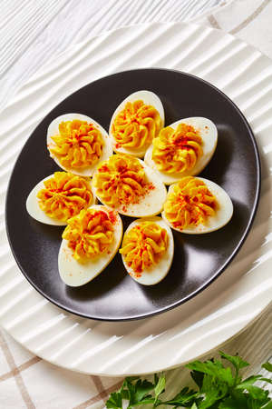 American hard-boiled eggs stuffed with a mix of egg yolks, dijon mustard, mayonnaise, apple cider vinegar sprinkled with smoked paprika on a plate on a white wooden background, top view, close-up