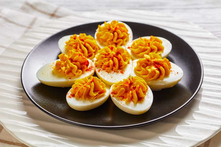 Stuffed egg halves with a mix of egg yolks, dijon mustard, mayonnaise, apple cider vinegar sprinkled with smoked paprika on a plate on a white wooden background, top view, close-up 免版税图像