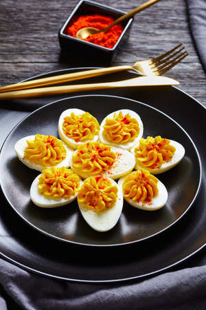 Picnic dish of hard-boiled eggs: deviled eggs filled with smashed egg yolks mustard, mayonnaise, white vinegar sprinkled with smoked paprika on a black plate on a dark wooden background, close-up