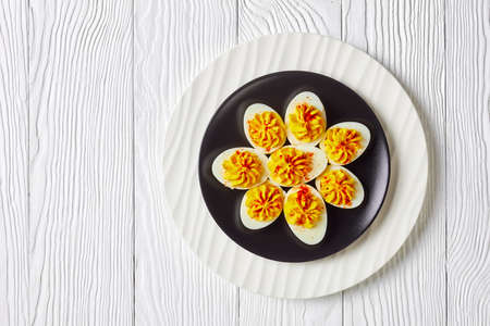 American deviled eggs of smashed egg yolks, dijon mustard, mayonnaise, apple cider vinegar sprinkled with smoked paprika on a black plate on a white wooden background, top view, copy space 免版税图像