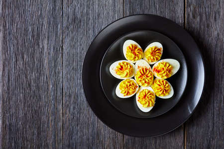 Easy keto recipe of deviled eggs filled with mustard, mayonnaise, white vinegar sprinkled with smoked paprika on a black plate on a dark wooden background, top view, copy space 免版税图像