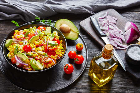 sweet corn salad with avocado, red onion slices and tomatoes in a black bowl on a dark wooden table with ingredients on dark old cutting board, mexican cuisine, landscape view from above, close-up