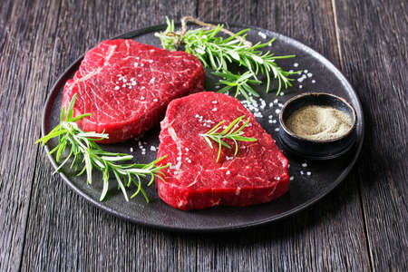 uncooked beef steaks with rosemary and finely ground black peppercorn on a black stone plate, landscape view from above