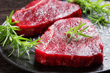 beef steaks with rosemary and finely ground black peppercorn and salt on a black stone plate, view from above, close-up