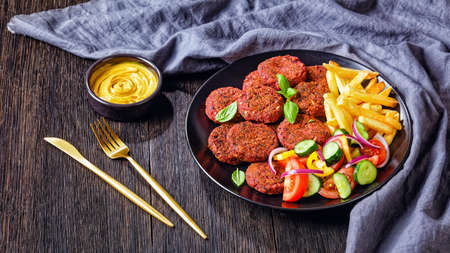 Vegan beetroot, mushrooms, black bean patties served with french fries and tomato, cucumber red onion salad on a black plate with nutritional yeast sauce on a dark wooden table, close-up Archivio Fotografico