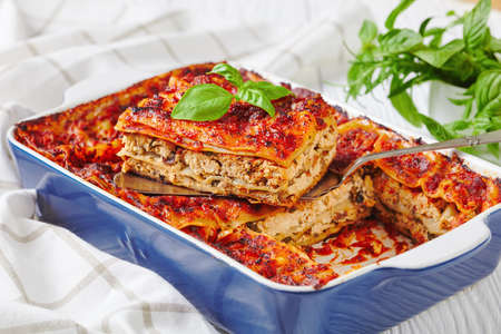 Italian lasagna casserole with firm tofu, mushrooms, tomato sauce baked on the oven, served on a baking dish with fresh basil on a white wooden background, close-up