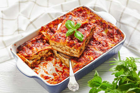 Meatless low-fat lasagna with firm tofu, mushrooms, tomato sauce, Italian seasoning, baked on the oven, served on a baking dish with fresh herbs on a white wooden background, close-up