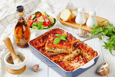 Plant-based lasagna with tofu, mushrooms, passata sauce in a baking dish served with a fresh salad of lettuce, tomato, cucumber, red onion and basil leaves on a white wooden background, close-up