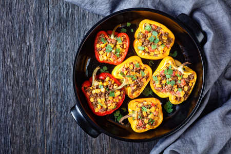 stuffed bell peppers with ground beef, corn and cheese in a black baking dish on a wooden table, horizontal view from above, flat lay, free space Stock fotó - 155445448