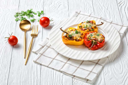 classic stuffed bell peppers with ground beef, corn and cheese on a white plate on a wooden table with golden cutlery, horizontal view from above