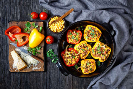 stuffed bell peppers with ground beef, corn and cheese in a black baking dish on a wooden table with ingredients on a cutting board, horizontal view from above, flat lay, free space Stock fotó - 155445451