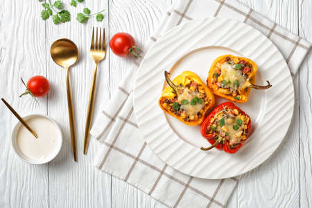 stuffed bell peppers with ground beef, corn and cheese on a white plate on a wooden table with golden cutlery, horizontal view from above, flat lay, free space Stock fotó - 155445453