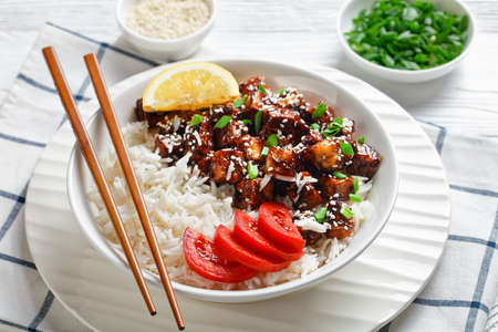 Teriyaki baked tofu with rice sprinkled by spring onion, sesame seeds, japanese cuisine, served with rice, sliced tomato, lemon on a white bowl with chopsticks on a white wooden background, close-up Stock fotó - 155445455