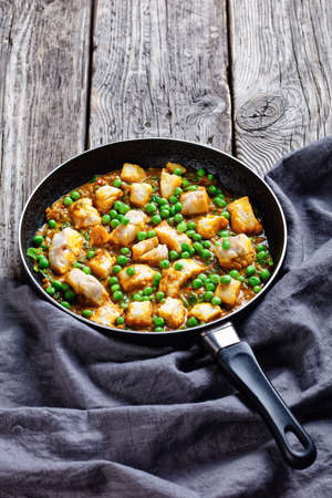 hot cod fish curry with green peas and spinach in a skillet on a dark wooden rustic table with gray cloth, vertical view from above Фото со стока
