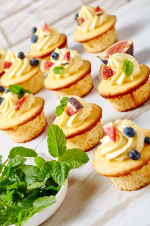 delicious cupcakes with buttercream and fresh berries and mint on a marble table, vertical view from above, close-up