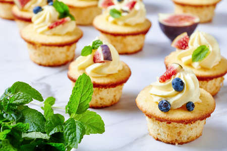 delicious cupcakes with buttercream and fresh berries and mint on a marble table, landscape view from above, close-up
