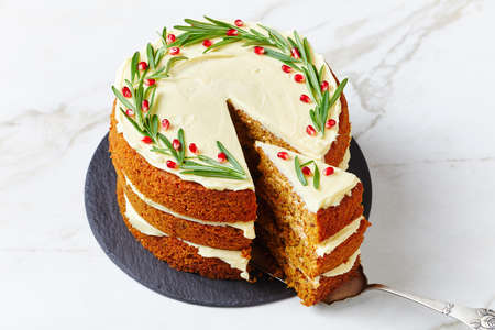 Traditional carrot cake of three sponge cake layers with cream cheese frosting, decorated with rosemary sprigs and pomegranate seeds, served on a white background