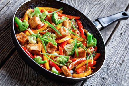 close-up of kung pao tofu with mixed peppers, broccoli and scallions in a skillet on a rustic wooden table, chinese cuisine, landscape view from above