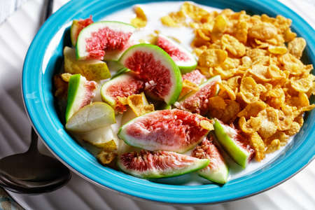 Blue bowl with natural plain yogurt with crispy cornflakes, figs, pear served on a white wooden background, top view, close-up
