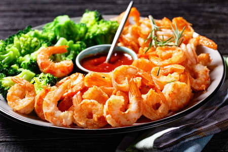 Garlic butter prawns or shrimps deshelled and fried served with steamed broccoli, ketchup, and lime on a plate with rosemary sprigs and cutlery on a dark wooden background, top view, close-up