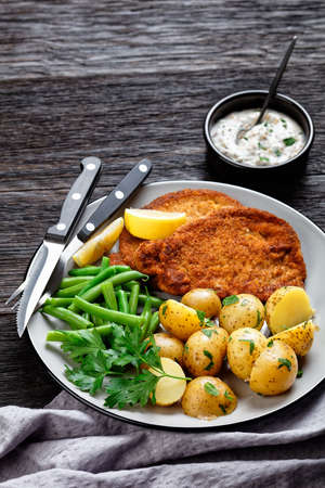 German pork schnitzel with young potatoes, green beans with cutlery served on a plate with lemon wedges, and mayonnaise based sauce on a dark wooden background, top view, close-up
