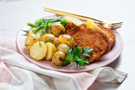 Breaded pork schnitzel with young potatoes, green beans with cutlery served on a pink plate with lemon wedges, on a light stone background, top view, close-up