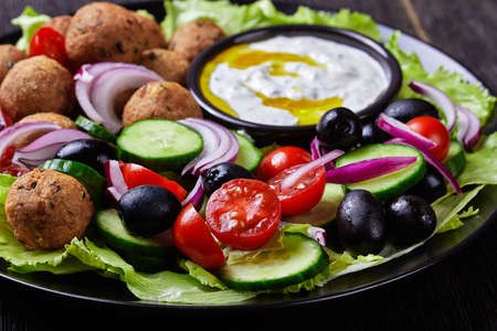 Mediterranean platter of falafels, tomatoes, cucumber, red onion, black olives, on the fresh salad leaves served with tzatziki sauce served on a black plate on a dark wooden background, close-up