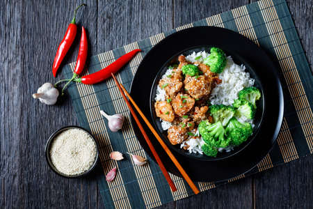 General Tso's Chicken crispy Chinese chicken bites in a black bowl with rice and steamed broccoli florets, horizontal view from above, flat lay