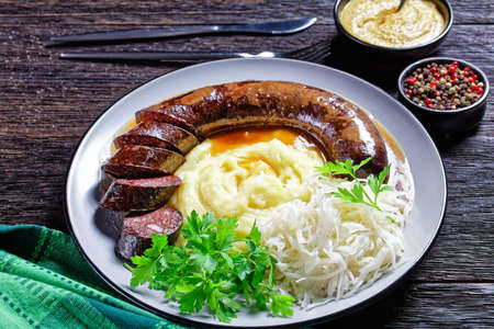 German food: blutwurst or blood sausage served on a plate with sauerkraut, mashed potato parsley, mustard, and peppercorns on a dark wooden table, top view, close-up