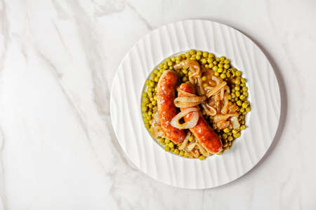 English meal: roasted pork sausages with peas and onion gravy on a white plate on a white marble background, top view, copy space