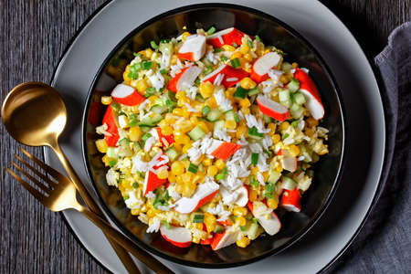 Crab salad of surimi sticks with vegetables: corn, cucumbers, scallion, eggs, jasmine rice with lime and mayonnaise dressing served in a black bowl on a dark wooden background, top view, close-up