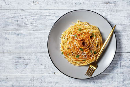 Pasta mollicata: spaghetti with anchovies and toasted breadcrumbs, parmesan cheese, and parsley - traditional southern Italy dish, served on a plate on a white wooden table, top view, copy space