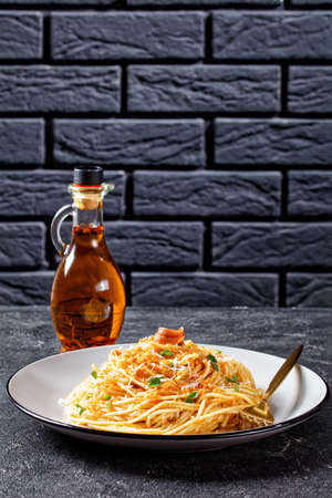 Pasta mollicata: spaghetti with anchovies and toasted breadcrumbs, parmesan cheese, and parsley - traditional southern Italy dish, served on a plate on a dark concrete background, top view, close-up