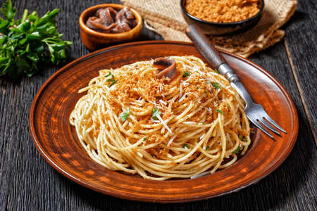 Pasta mollicata: spaghetti with anchovies and toasted breadcrumbs, parmesan cheese, and parsley - traditional southern Italy dish, served on a plate on a dark wooden background, top view, close-up