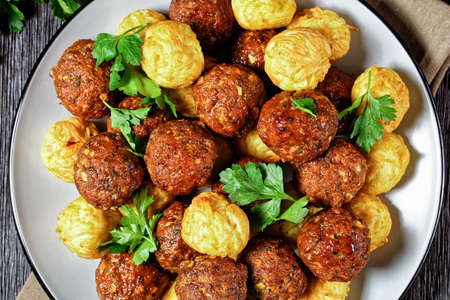 Italian meatballs of ground beef and pork with pasta balls served on a plate with cutlery on a dark wooden background with fresh parsley and tomato sauce, top view, close-up
