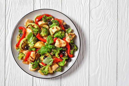 Vegetable and chicken roast with young potato, pepper, courgette, olives, sprinkled with balsamic vinegar and basil on top, served on a plate on white wooden background, top view, copy space 写真素材