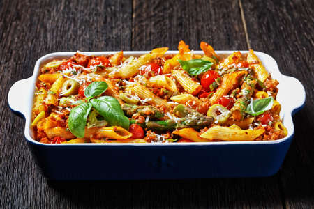 ground turkey penne pasta bake with asparagus, tomatoes and olives in a baking dish on a dark wooden table, italian cuisine