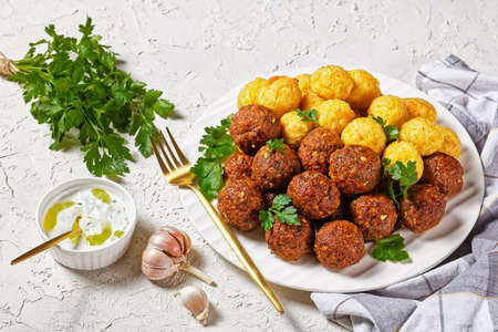 Meatballs of ground beef and pork with spaghetti balls served on a white plate with fork on a white concrete table with fresh parsley and greek yogurt sauce tzatziki, top view, close-up 写真素材