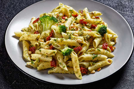Broccoli pesto penne pasta with sundried tomatoes and pine nuts on a plate, horizontal view from above, italian cuisine, close-up
