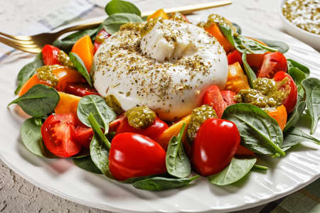 close-up of Spinach, Tomato and Burrata cheese Salad with Basil Pesto Dressing on a white plate, italian cuisine 写真素材