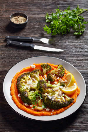 grilled broccoli steak with pumpkin mash topped  with crumbled feta cheese, vegetarian recipe, vertical view from above