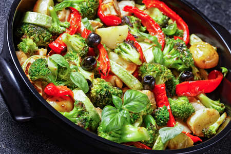 Vegetable and chicken bake of new potato, broccoli, red pepper, courgette, black olives with fresh basil leaves on top, served on a black baking dish on concrete background, top view, close-up 写真素材