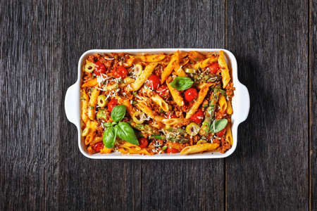 ground turkey penne pasta bake with asparagus, tomatoes and olives in a baking dish on a dark wooden table, italian cuisine, flat lay, free space