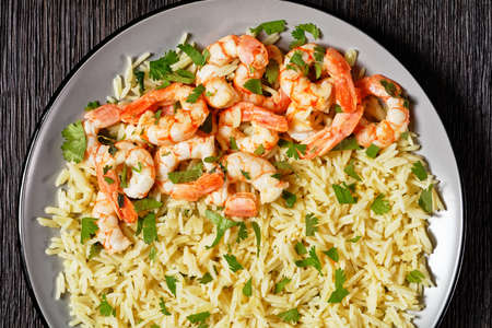 Mexican dish lime shrimps with cilantro and long grain rice cooked with chicken broth served on a plate on a dark wooden background, top view, close-up