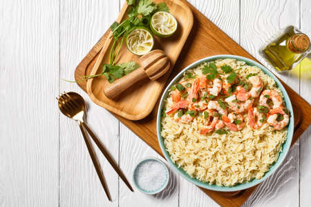 American cuisine lime shrimps with cilantro and long grain rice cooked with chicken broth served on a blue plate on a white wooden background with olive oil, top view, close-up