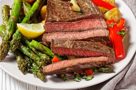 beef steak with barbequed new baby potatoes, asparagus, lemon and red pepper on a white plate with barbecue sauce on a wooden table, close-up