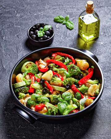 Broccoli and chicken bake with new potato, red pepper, courgette, black olives with fresh basil leaves on top, served on a black baking dish on concrete background, top view, close-up, vertical view