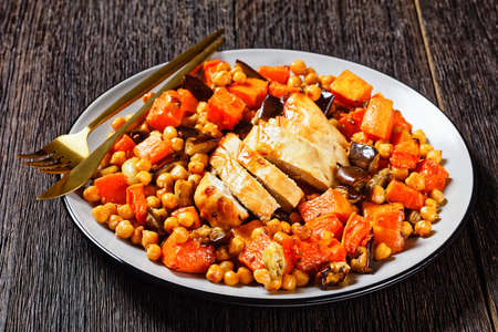 Traybake salad of chickpea with butternut, eggplant, with lemon and baked chicken breast, served on a plate with cutlery on a dark wooden table, top view, close-up 写真素材